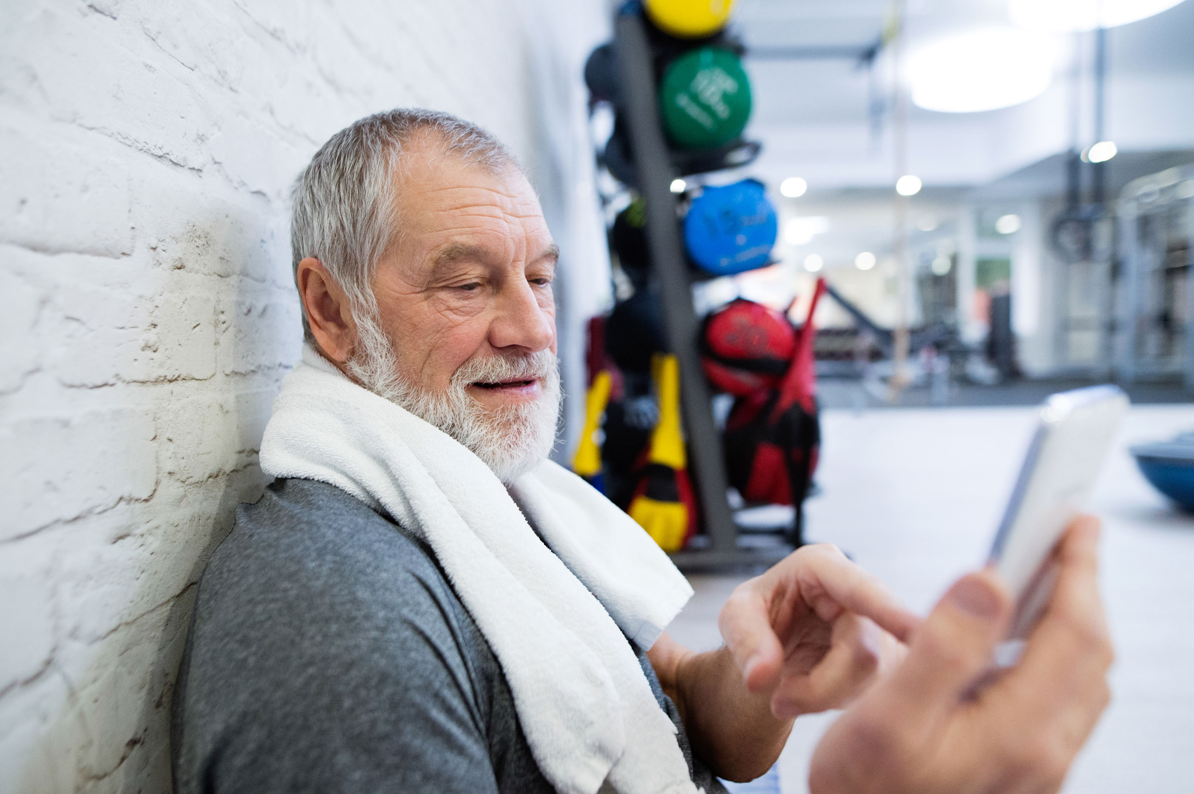 An older adult or technophobic personal training client overcomes challenges with fitness technology