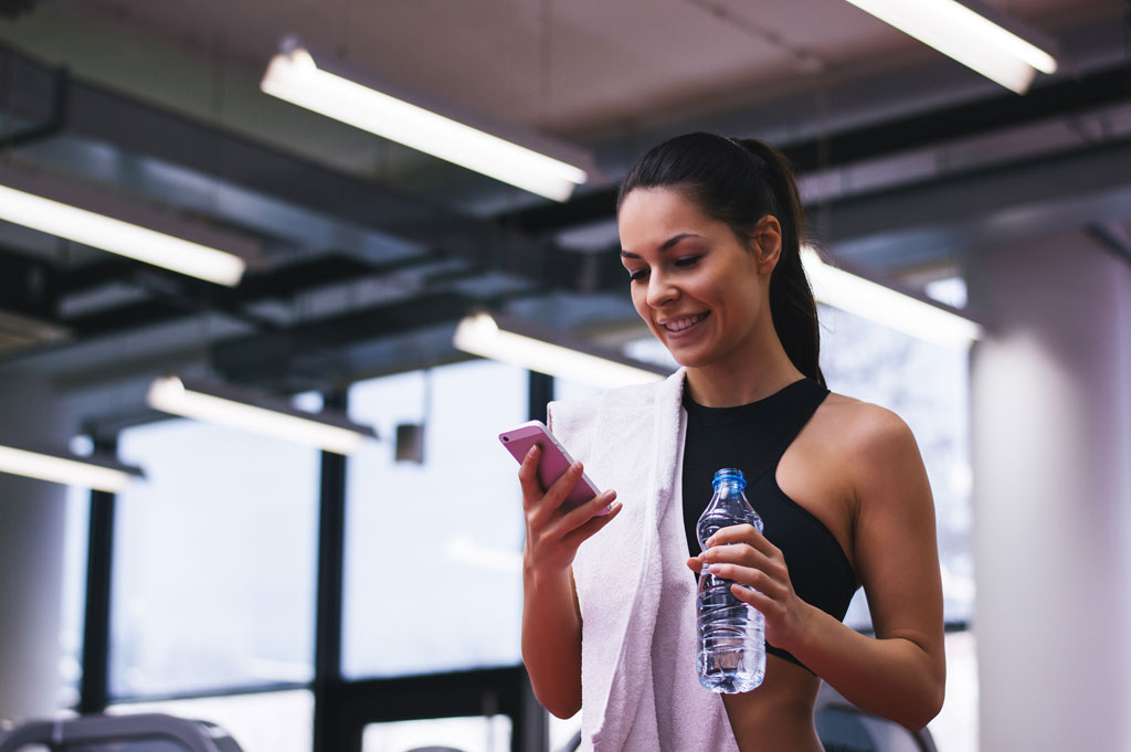 Woman logs her workouts using online personal training app